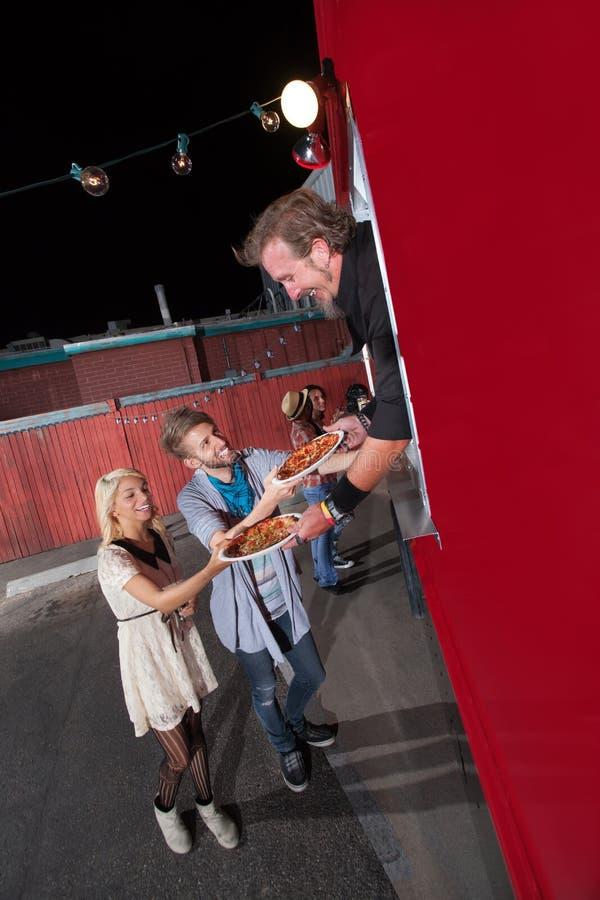 Adolescentes que piden la pizza del camión de la comida fotos de archivo