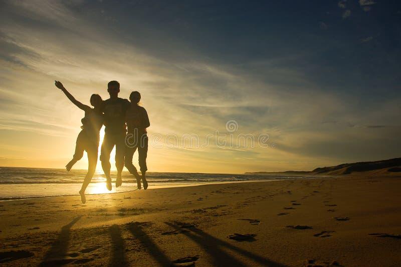Adolescentes que saltam contra o por do sol fotografia de stock