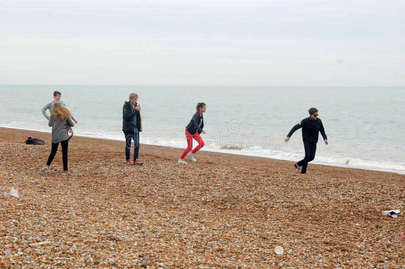 Adolescentes que se divierten en la playa de Hastings foto de archivo libre de regalías