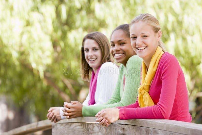 Adolescentes que se inclinan en el pasamano de madera imagen de archivo libre de regalías