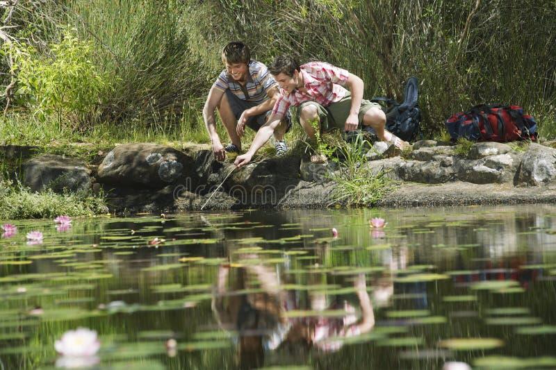 Adolescentes que se ponen en cuclillas por el lago foto de archivo