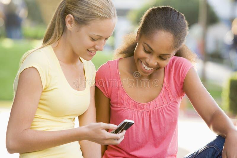 Adolescentes que se sientan afuera imagen de archivo