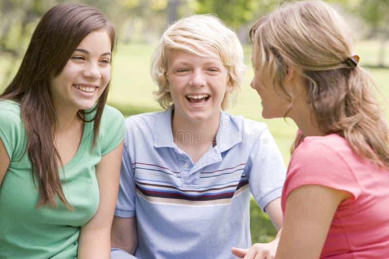 Adolescentes que se sientan y que conversan fotografía de archivo libre de regalías
