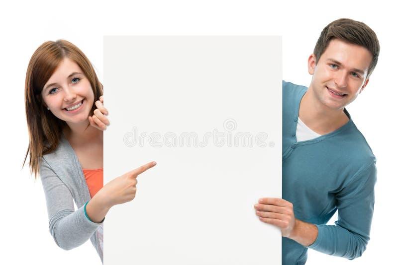 Adolescentes que se sostienen en una tarjeta en blanco fotografía de archivo libre de regalías