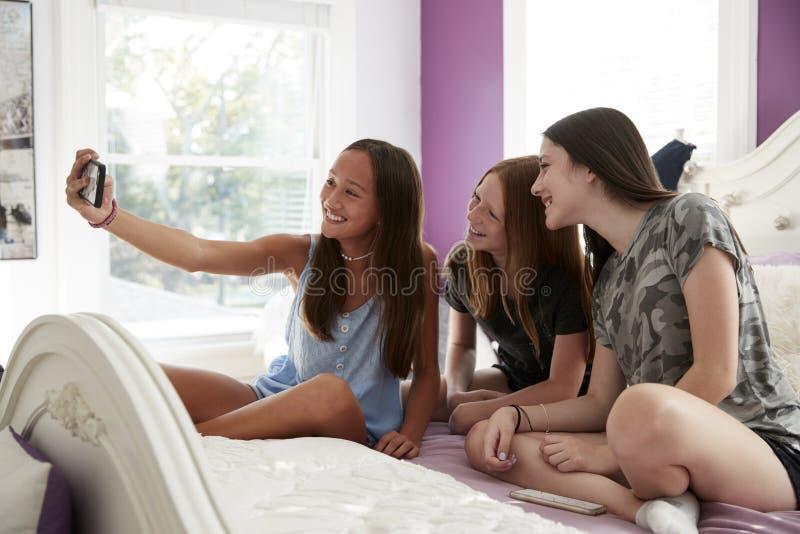 Adolescentes que sentam-se em uma cama que toma junto um selfie foto de stock