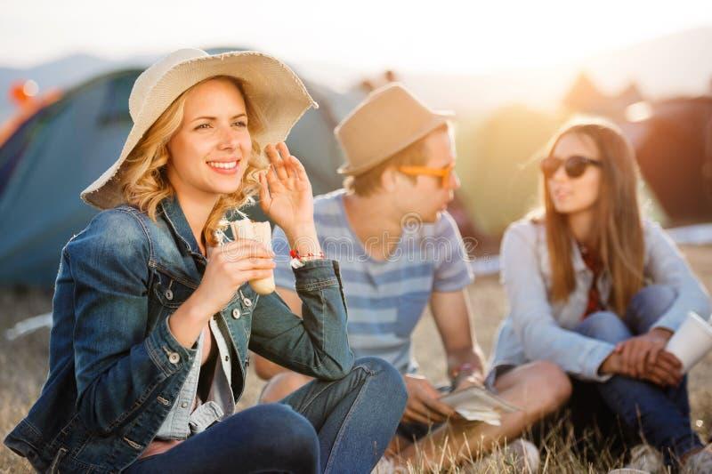 Adolescentes que sentam-se na terra na frente das barracas, descansando imagem de stock