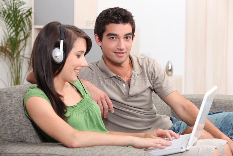 Adolescentes que sentam-se no sofá fotos de stock