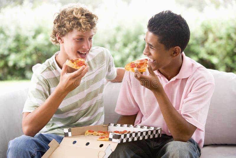 Adolescentes que sentam-se no sofá que come a pizza fotos de stock royalty free