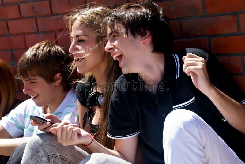 Adolescentes que sentam-se por uma rua fotografia de stock royalty free