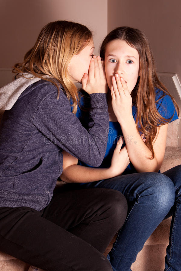Adolescentes que sussurram segredos imagens de stock