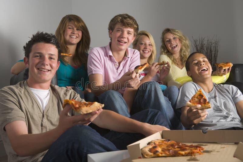 Adolescentes que têm o divertimento e que comem a pizza fotos de stock royalty free