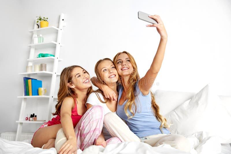 Adolescentes que tomam o selfie pelo smartphone em casa imagens de stock