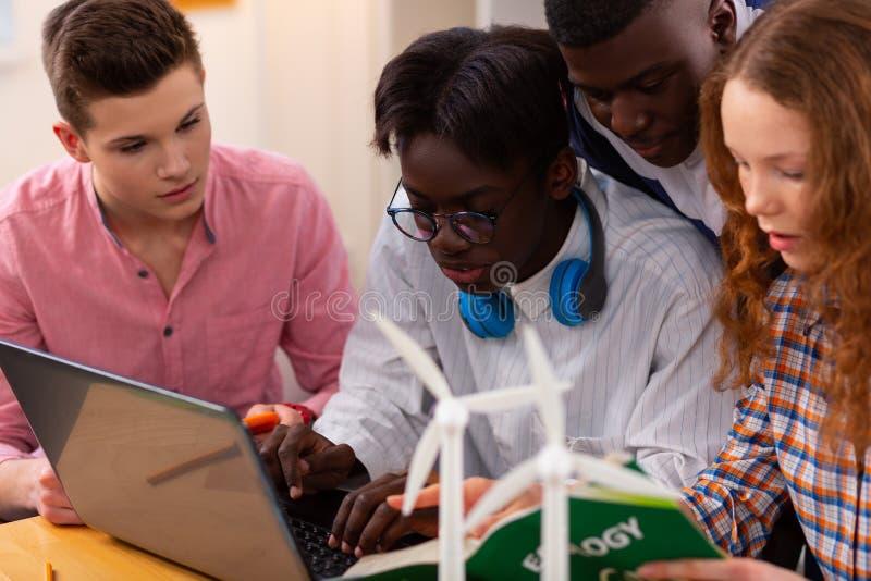 Adolescentes que trabajan en proyecto final en ecología y fuentes de energía fotografía de archivo