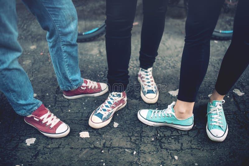 Adolescentes rebelde dos jovens que vestem as sapatilhas ocasionais, andando no concreto sujo Sapatas e sapatilhas de lona em adu fotos de stock