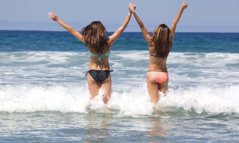 Adolescentes s'attaquant dans l'océan à la plage photographie stock libre de droits