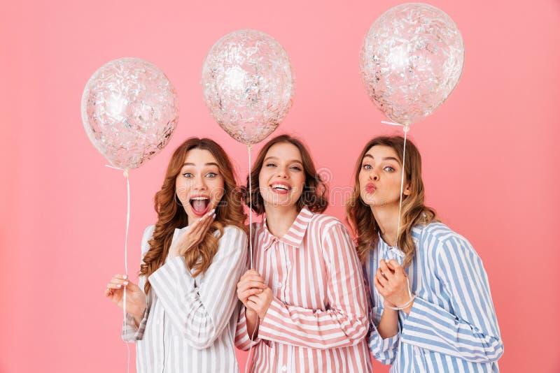 Adolescenti adorabili 20s in pigiami a strisce variopinti che posano sopra fotografia stock