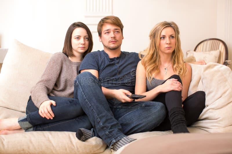 Adolescenti affascinati che si siedono televisione di sorveglianza fotografia stock