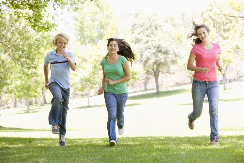 Adolescenti che funzionano attraverso la sosta fotografia stock