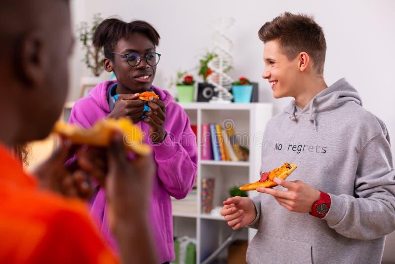 Adolescenti che indossano le maglie con cappuccio alla moda che parlano e che mangiano pizza immagine stock libera da diritti