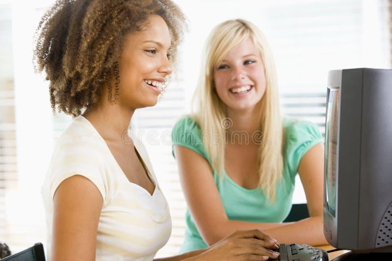Adolescenti che per mezzo del desktop computer immagini stock libere da diritti