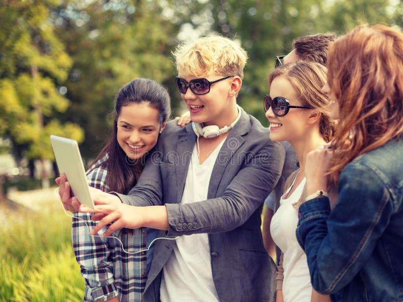 Adolescenti che prendono foto con il pc della compressa fuori fotografia stock