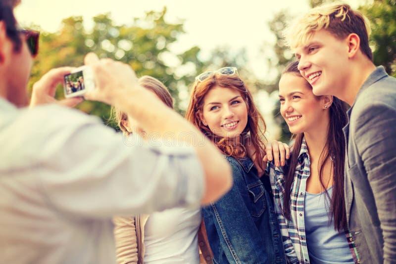 Adolescenti che prendono foto con la macchina fotografica digitale fuori immagini stock