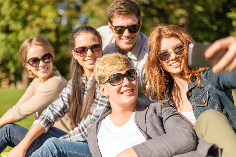 Adolescenti che prendono foto con lo smartphone fuori fotografia stock libera da diritti