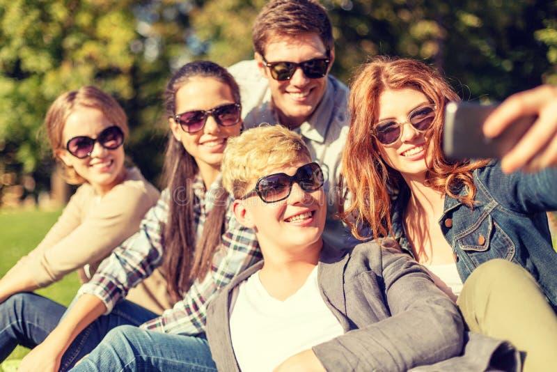 Adolescenti che prendono foto con lo smartphone fuori fotografie stock