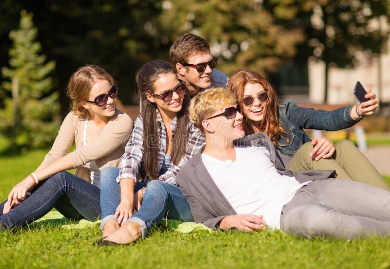 Adolescenti che prendono foto fuori con lo smartphone fotografia stock