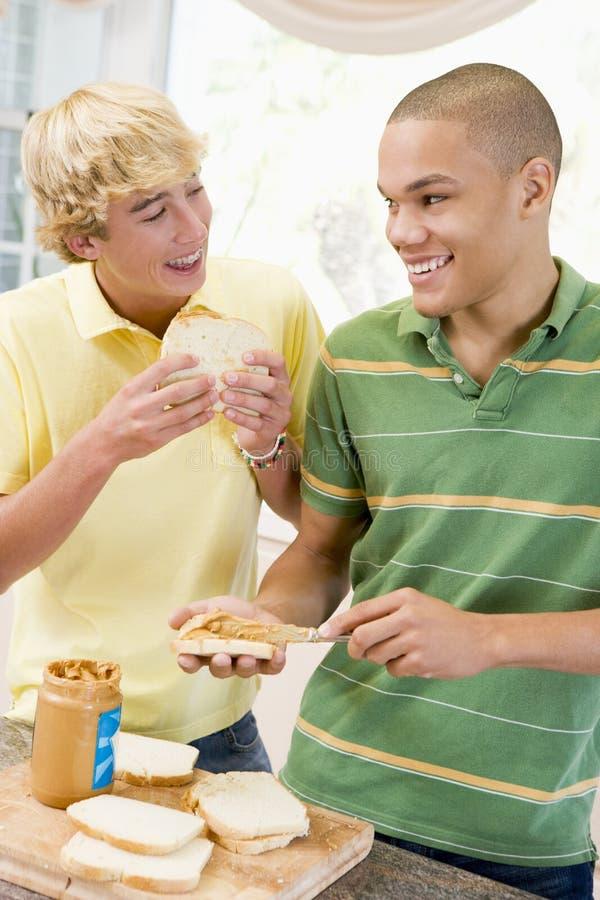 Adolescenti che producono i panini immagini stock