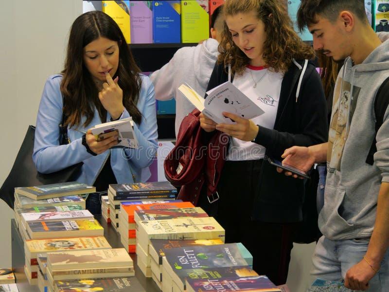 Adolescenti che scelgono un libro in libreria variopinta fotografia stock libera da diritti