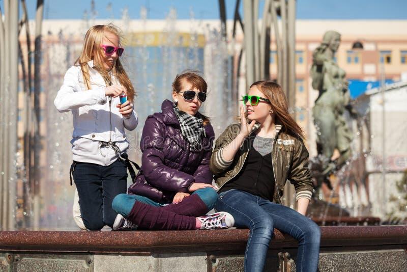 Adolescenti che si rilassano contro una fontana della città immagine stock libera da diritti