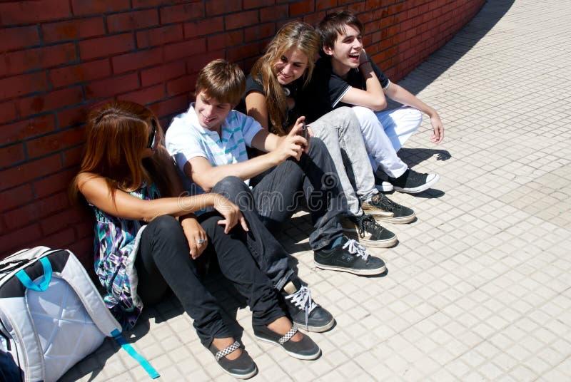 Adolescenti che si siedono da una via fotografia stock