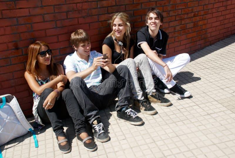 Adolescenti che si siedono da una via immagini stock