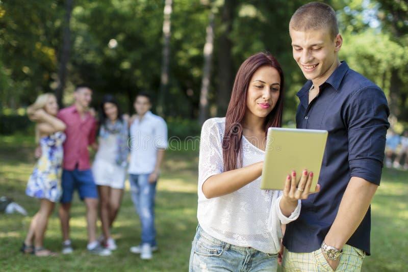 Adolescenti con la compressa nel parco fotografie stock