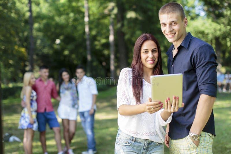 Adolescenti con la compressa in parco fotografia stock