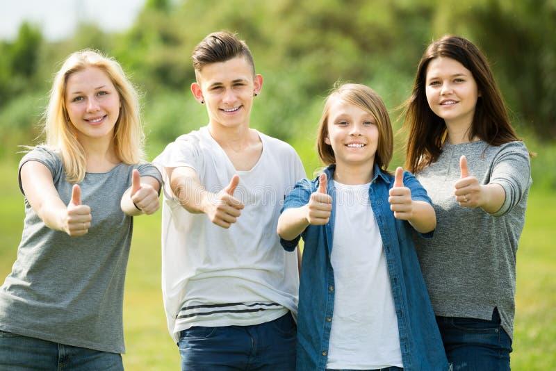 Adolescenti degli amici che stanno e che tengono i pollici su immagini stock libere da diritti