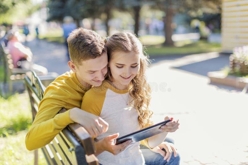 Adolescenti delle coppie su un banco immagine stock
