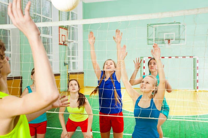 Adolescenti e ragazze che giocano il gioco di pallavolo fotografia stock
