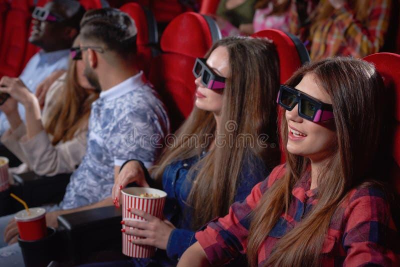 Adolescenti graziosi che godono della commedia in cinema fotografia stock libera da diritti