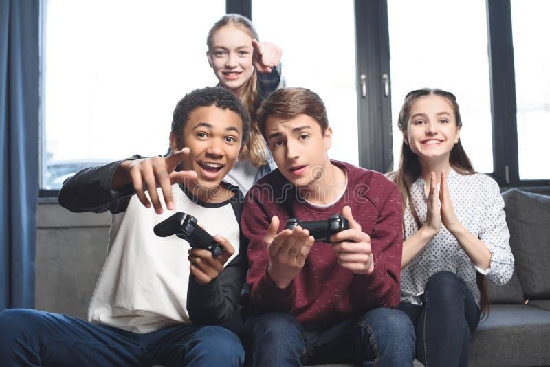 Adolescenti multiculturali felici che giocano i video giochi con le leve di comando a casa immagine stock