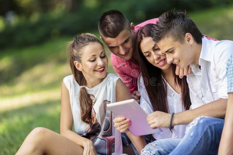 Adolescenti nel parco con la compressa fotografia stock libera da diritti