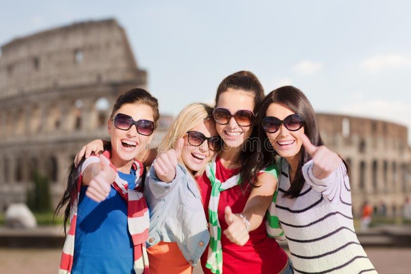 Adolescenti o donne felici che mostrano i pollici su fotografia stock libera da diritti