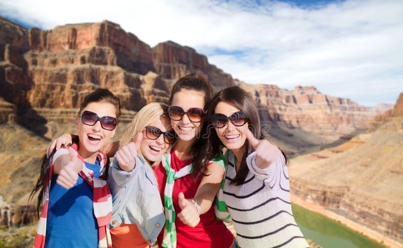 Adolescenti o giovani donne che mostrano i pollici su fotografia stock
