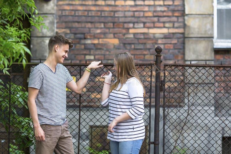Adolescenti, ragazzo e ragazza parlanti sulla via stringimento fotografia stock