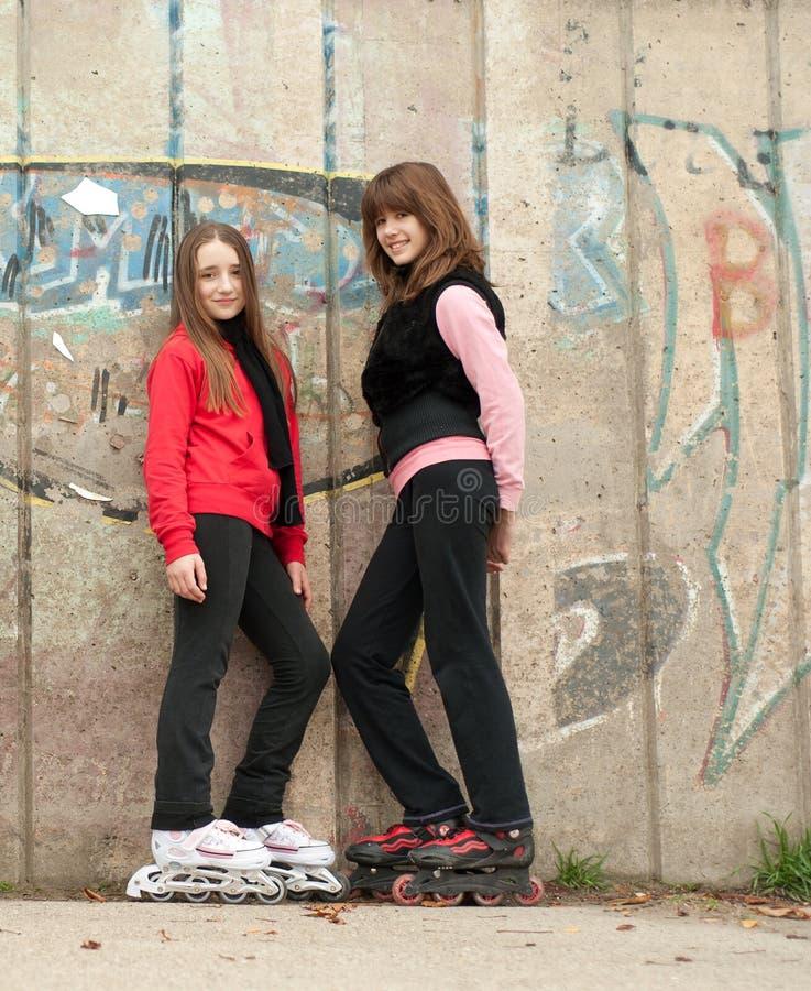 Adolescenti sulla posizione dei pattini di rullo esterna fotografia stock libera da diritti