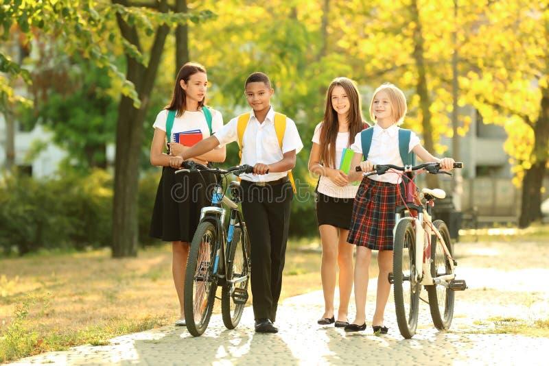 Adolescenti svegli con le biciclette che camminano nel parco fotografia stock libera da diritti