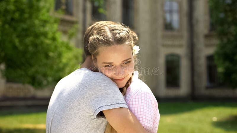 Adolescents étreignant, fille avec la fleur dans les cheveux appréciant la date, relations pures images libres de droits