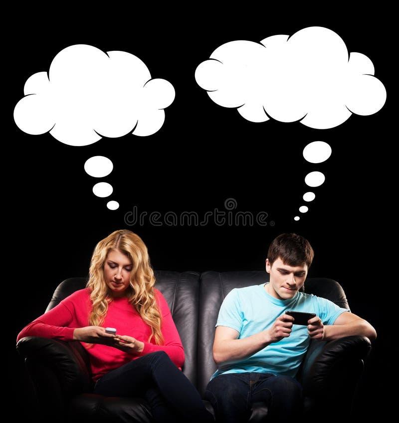 Adolescents dépendants de technologie sur un sofa image stock