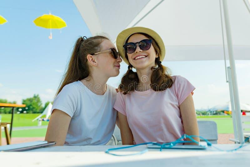Adolescents de filles ayant l'amusement, entretien, secret, rire Reposez-vous dans un café de rue, un jour d'été ensoleillé dans  photo libre de droits